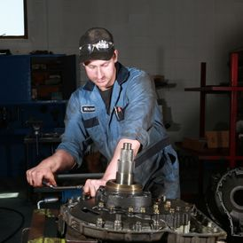 Employee fixing a heavy-duty truck part